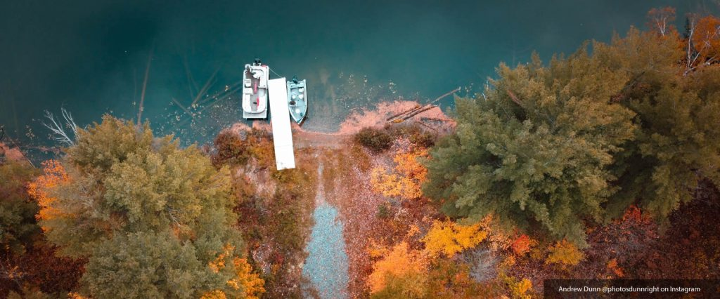 photo looking down of a lake and fall trees and a dock with boats