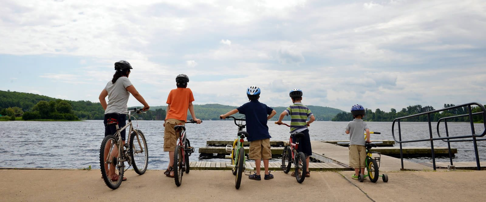 Kids look at the lake holding onto bikes
